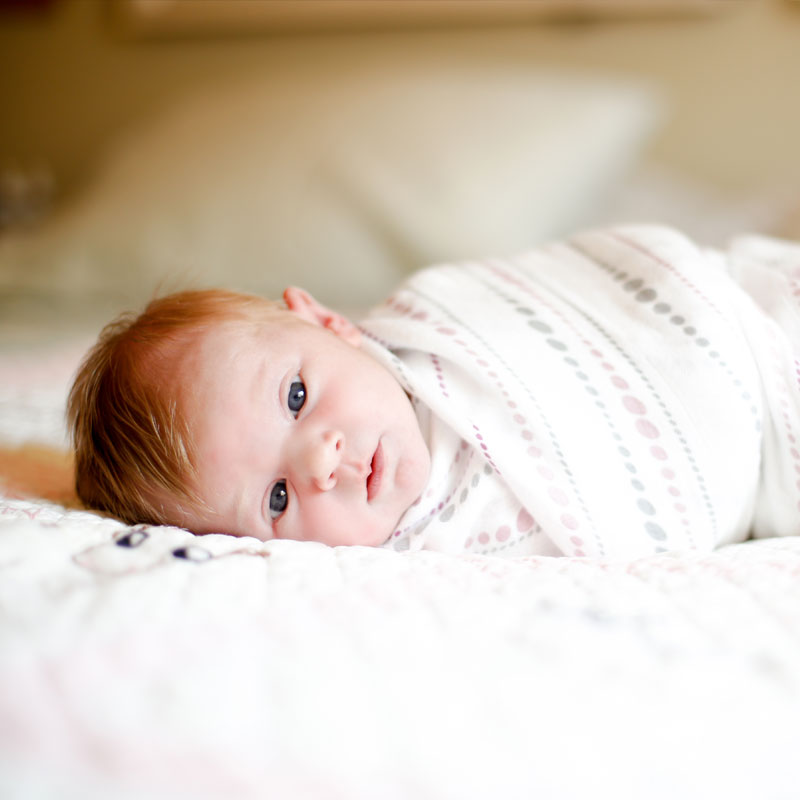 Midwives and Lactation Consulting, baby wrapped up on bed